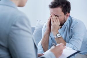 Man crying in therapist office trying to deal with depression.